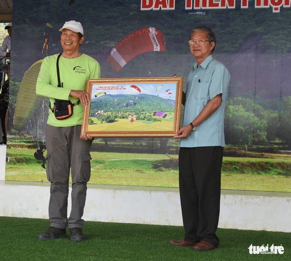 Cao Quang Liem (left), Tri Ton Party Secretary, hands a souvenir painting for Nguyen Huu Nam, the oldest pilot participating in a paragliding contest at Tri Ton District in the southern province of An Giang on November  28, 2020. Photo: Buu Dau/ Tuoi Tre