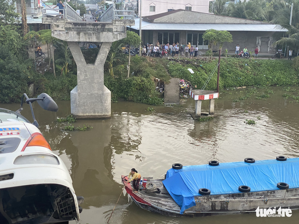 A boat is obstructed by a truck dangling from the remaining part of the Thien Ho Bridge on Nguyen Van Tiep canal after it collapsed due to the overweight truck in Cai Be District, Tien Giang Province, November 30, 2020. Photo: Hoai Thuong / Tuoi Tre