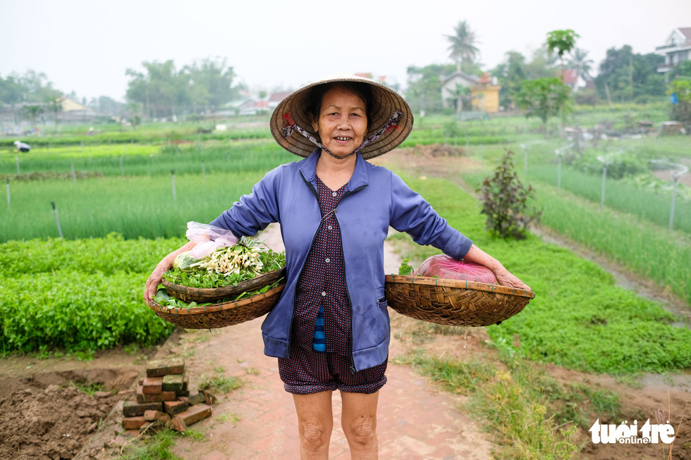 A Tra Que farmer is seen holding her harvests. Photo: Gia Thinh / Tuoi Tre