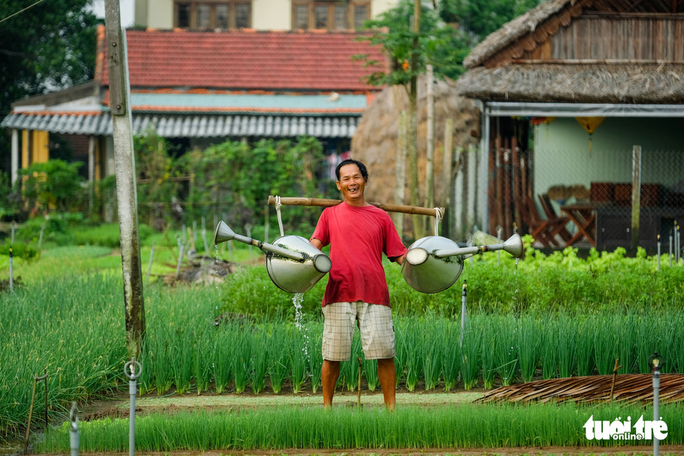 A Tra Que farmer waters his plants with watering cans. Photo: Gia Thinh / Tuoi Tre