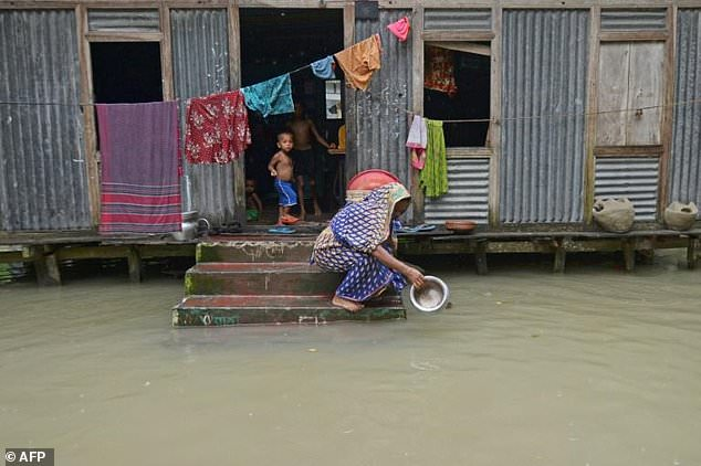 A woman washes her cooking pot in the flood waters outside her house in Sreenagar, Bangladesh on July 20, 2020.