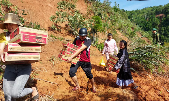 Teachers at Bo Trach Boarding High School for Ethnic Minority Students, in Bo Trach District, Quang Binh Province in north-central Vietnam, carry relief supplies near landslide site in this photo provided by Hoang Duc Hoa, the school's headmaster