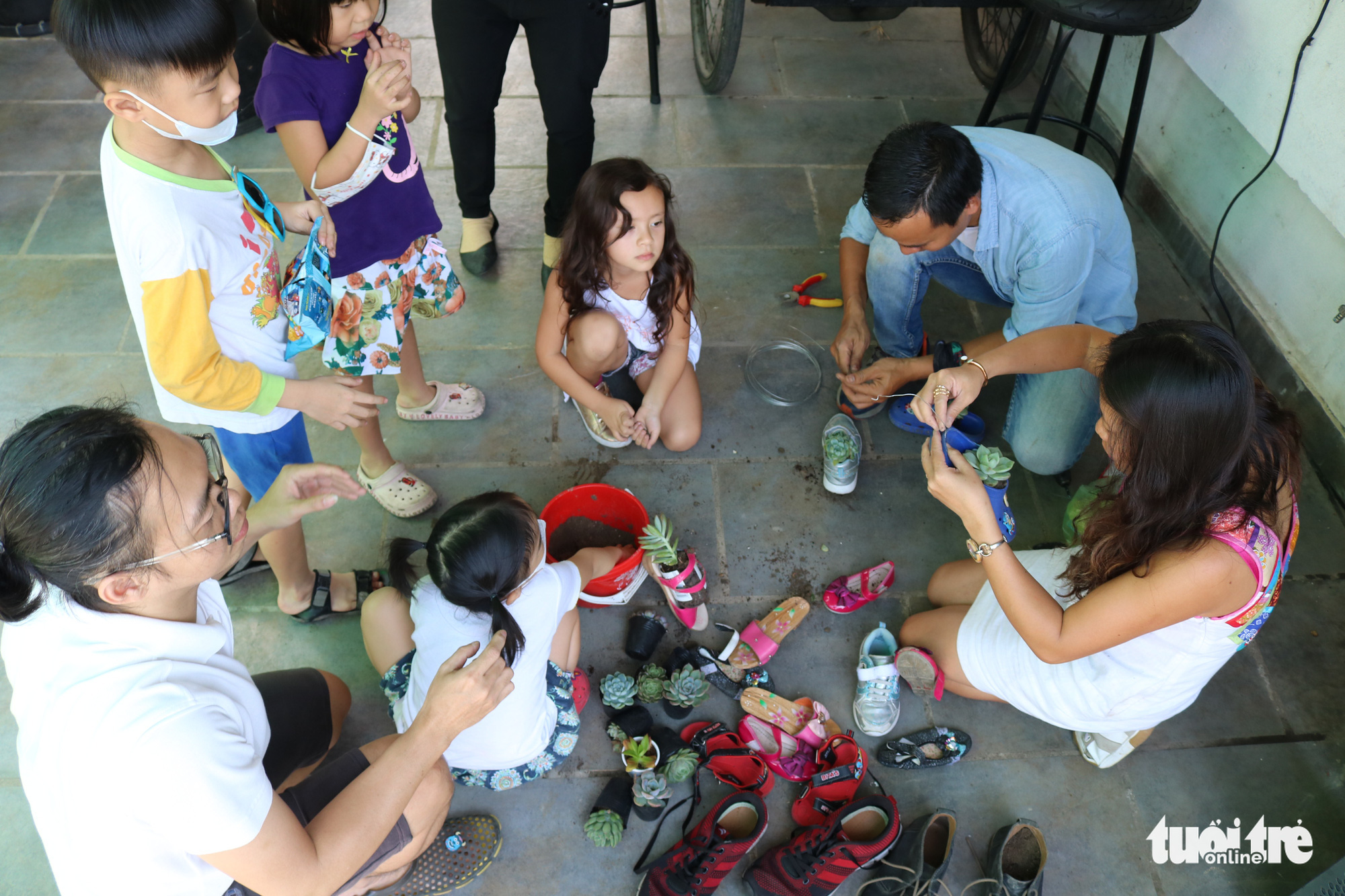 Young children make plant pots from used shoes at a recycling-themed coffee shop in District 2, Ho Chi Minh City. Photo: Hoang An / Tuoi Tre