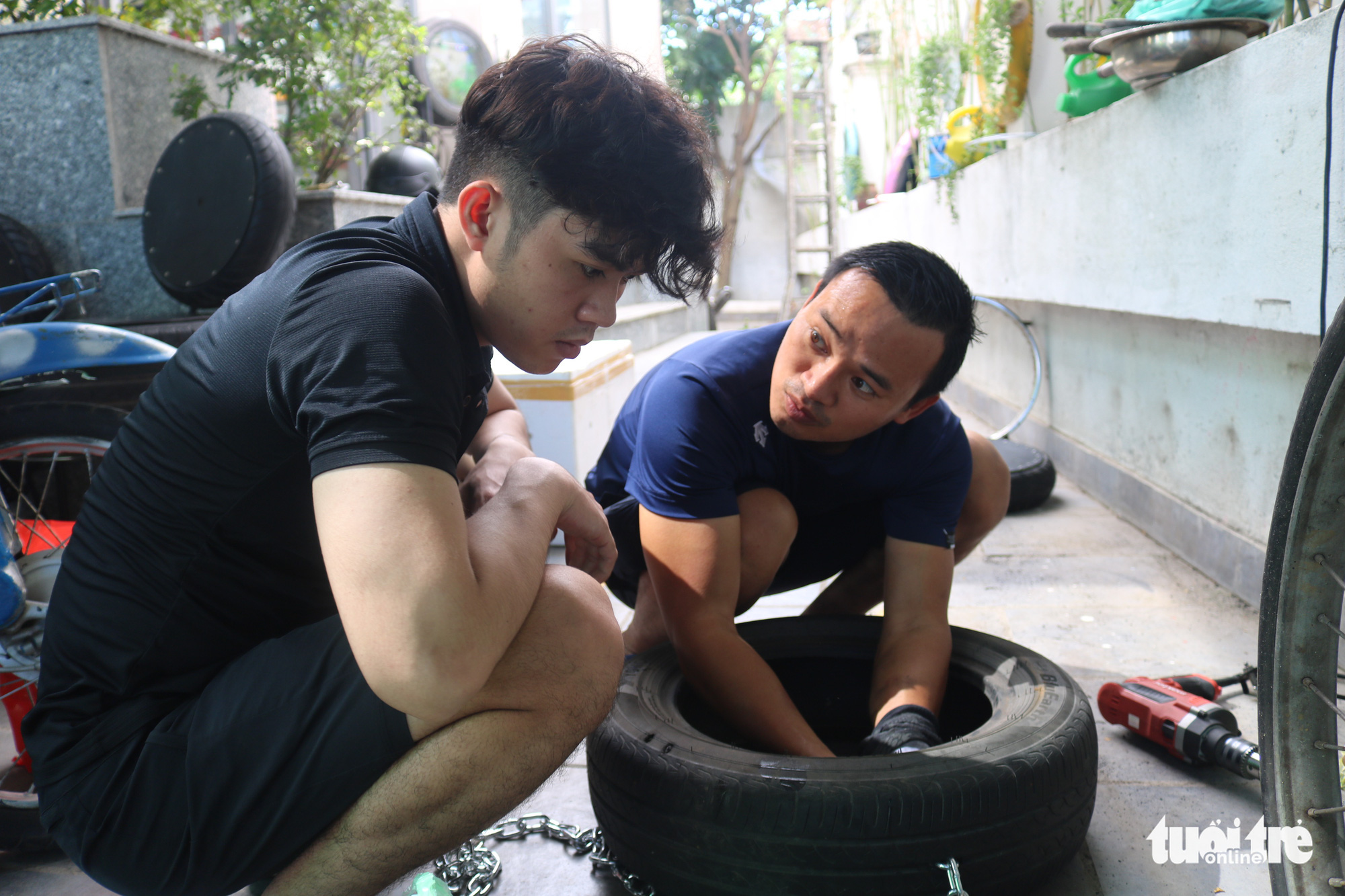 Nguyen Van Tho shows his employee how to recycle an old tire at his coffee shop in District 2, Ho Chi Minh City. Photo: Hoang An / Tuoi Tre