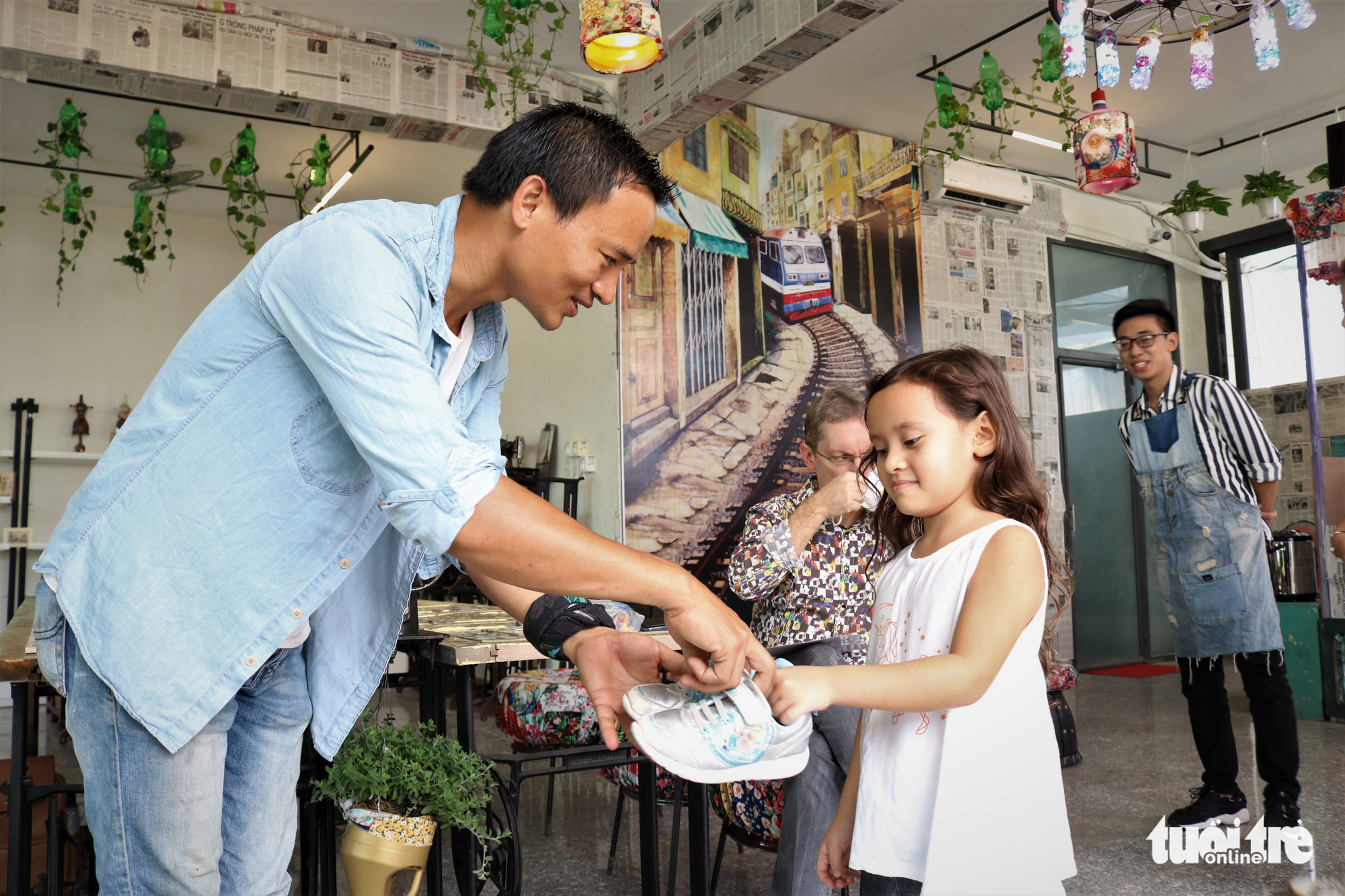 Nguyen Van Tho receives an old pair of shoes from a young customer at his coffee shop in District 2, Ho Chi Minh City. Photo: Hoang An / Tuoi Tre