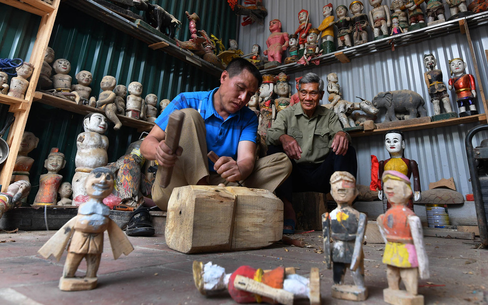 Dinh The Van teaches young artisan Dinh The Dung how to create and restore puppets. Photo: Hoang Ngoc Thanh / Tuoi Tre
