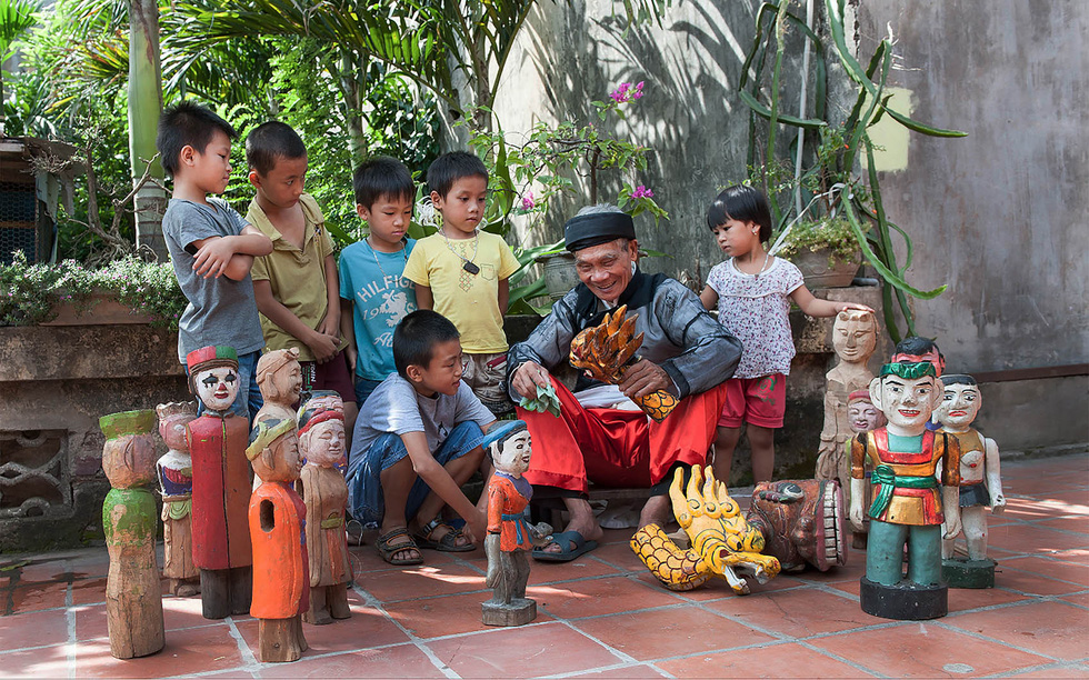 Veteran artisan shows off puppets to local children. Photo: Hoang Ngoc Thanh / Tuoi Tre