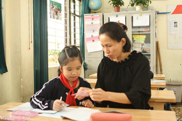Trinh Thi Lien (right) instructs a student how to do exercises at Xa Dan Middle School for students with hearing and speech disabilities, located in Hanoi, Vietnam. Photo: Vinh Ha / Tuoi Tre