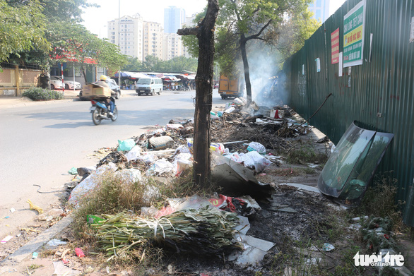 Piles of trash are seen in front of Nam Trung Yen Market in Cau Giay District.