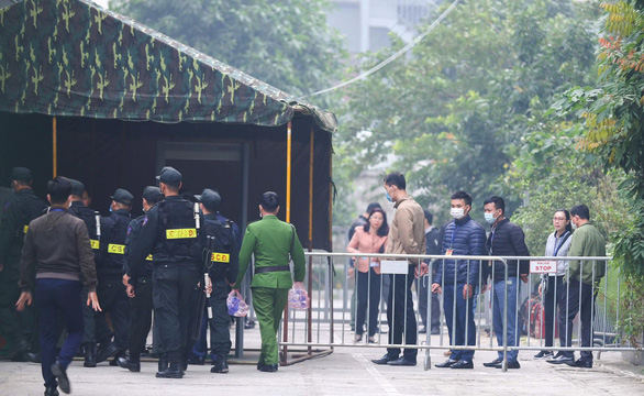Attendants of Nguyen Duc Chung's trial line up for security probe before entering the courtroom. Photo: Danh Trong / Tuoi Tre