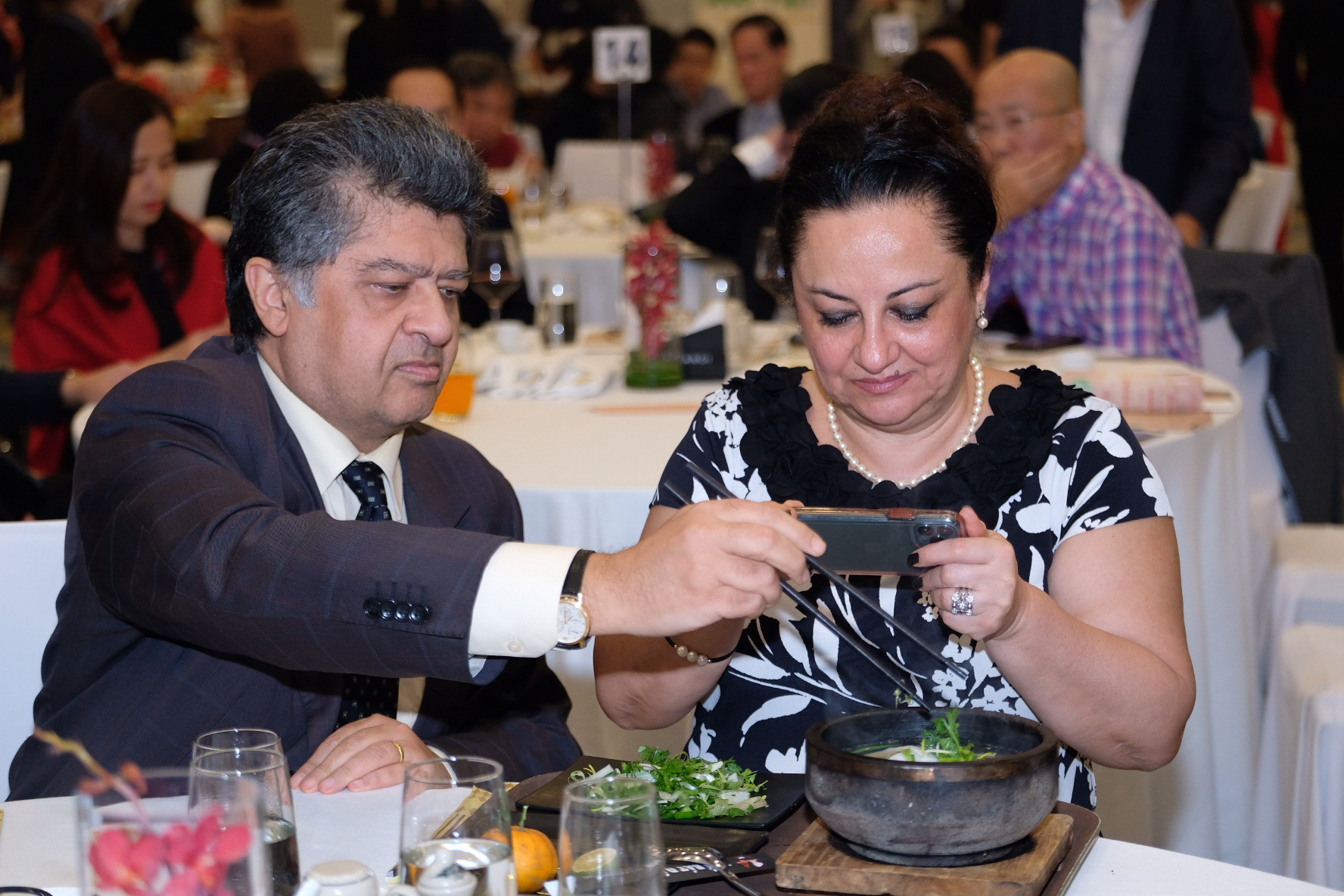 Vahram Kazhoyan, Armenia's ambassador to Vietnam, and his wife taste pho served in a stone bowl at the gala dinner of this year's 'Day of Pho' event in Hanoi, December 10, 2020. Photo: Nam Tran / Tuoi Tre