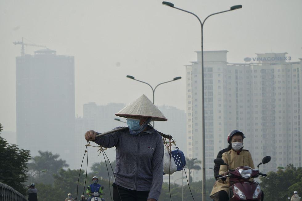 A street vendor is seen through the grey haze in Hanoi. Pham Tuan / Tuoi Tre