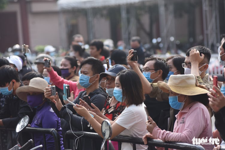 People live-stream the funeral in front of the Ministry of National Defense Funeral Home in Ho Chi Minh City, December 12, 2020. Photo: Duyen Phan / Tuoi Tre