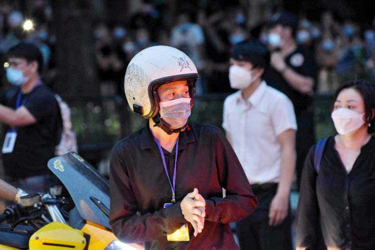 Vietnamese comedian Hoai Linh joins a motorcade to escort Chi Tai's body to Tan Son Nhat International Airport in Ho Chi Minh City, December 12, 2020. Photo: Duyen Phan / Tuoi Tre