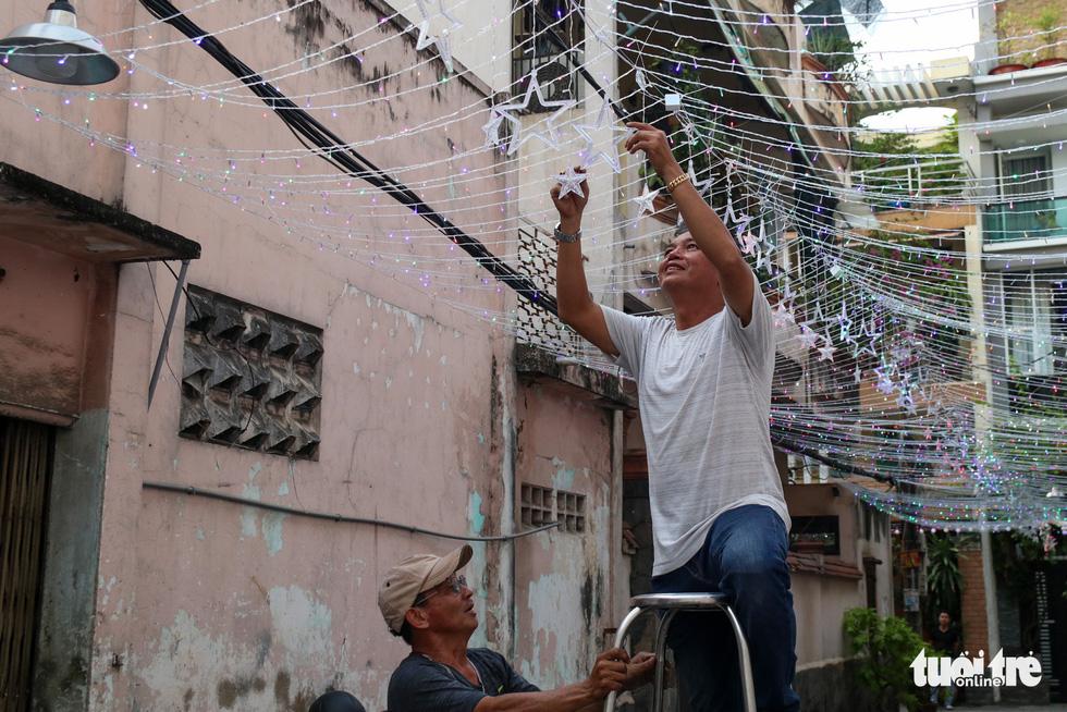 Residents of Mau Tam Catholic Parish install flashing lights on Hoang Van Thu Street of Ho Chi Minh City. Photo: Huu Huong / Tuoi Tre