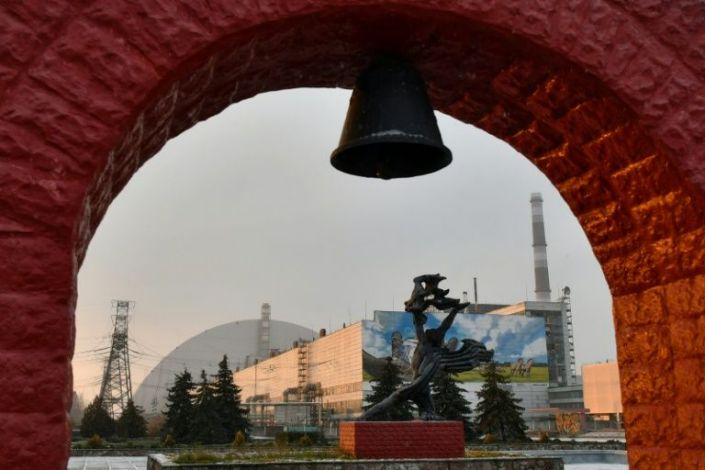 The sarcophagus of the destroyed fourth reactor can be seen behind a monument to the accident -- the 20th anniversary of the plant's final 2000 closure is on Wednesday. Photo: AFP