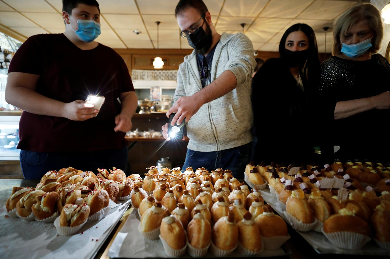 Customers take photos of 'Abu Dhabi' doughnuts, a date-flavoured confectionery inspired by Israel's new relations with the United Arab Emirates, as doughnuts are a popular fare in Israel during the current holiday of Hanukkah, in which Jews traditionally eat deep-fried delicacies, at a patisserie in Jerusalem December 13, 2020. Photo: Reuters