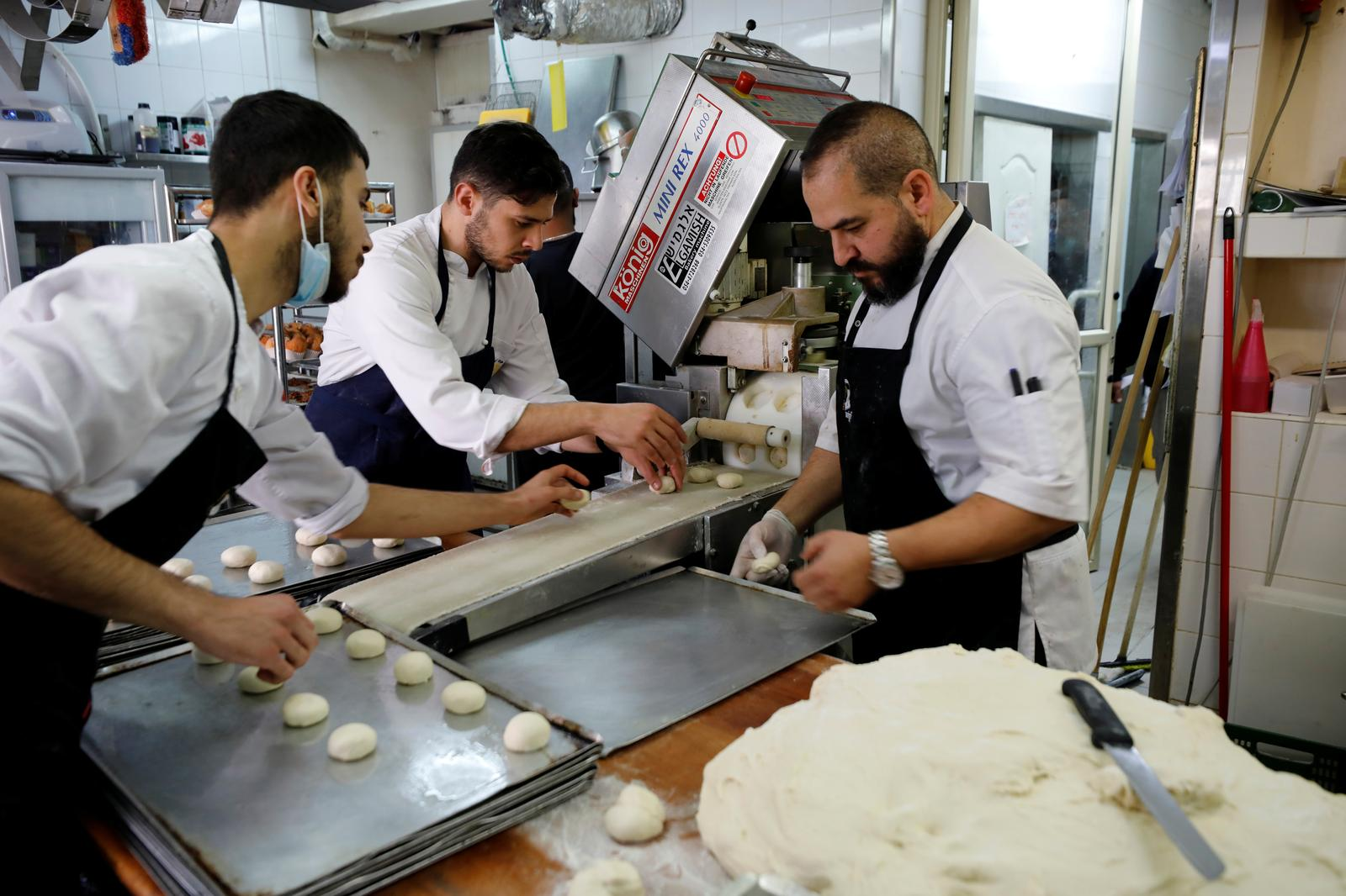 Confectioners make 'Abu Dhabi' doughnuts, a date-flavoured confectionery inspired by Israel's new relations with the United Arab Emirates, as doughnuts are a popular fare in Israel during the current holiday of Hanukkah, in which Jews traditionally eat deep-fried delicacies, at a patisserie in Jerusalem December 13, 2020. Photo: Reuters