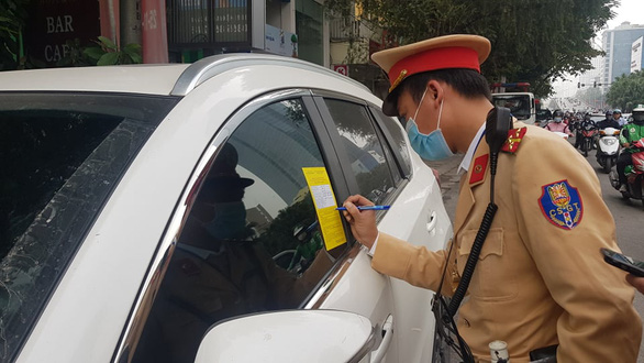 A traffic police officer fills in a parking ticket stuck on a windshield of a car on a street in Hanoi on December 14, 2020. Photo: Quang Hieu