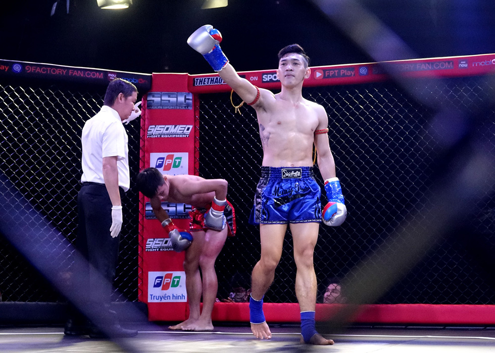 Huynh Hoang Phi (blue) salutes the audience after claiming victory over Do Huy Hoang (red). Photo: Hoang Tung / Tuoi Tre