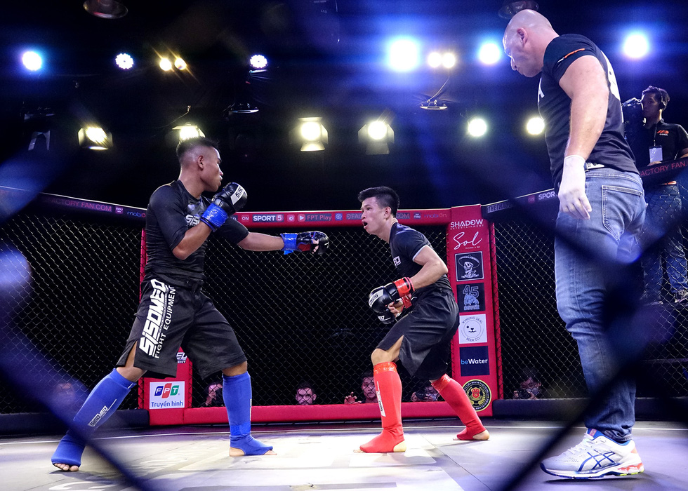 Bui Truong Sinh (red) and Dinh Van Huong (blue) are seen fighting in the first amateur MMA match in Vietnam. Photo: Hoang Tung / Tuoi Tre