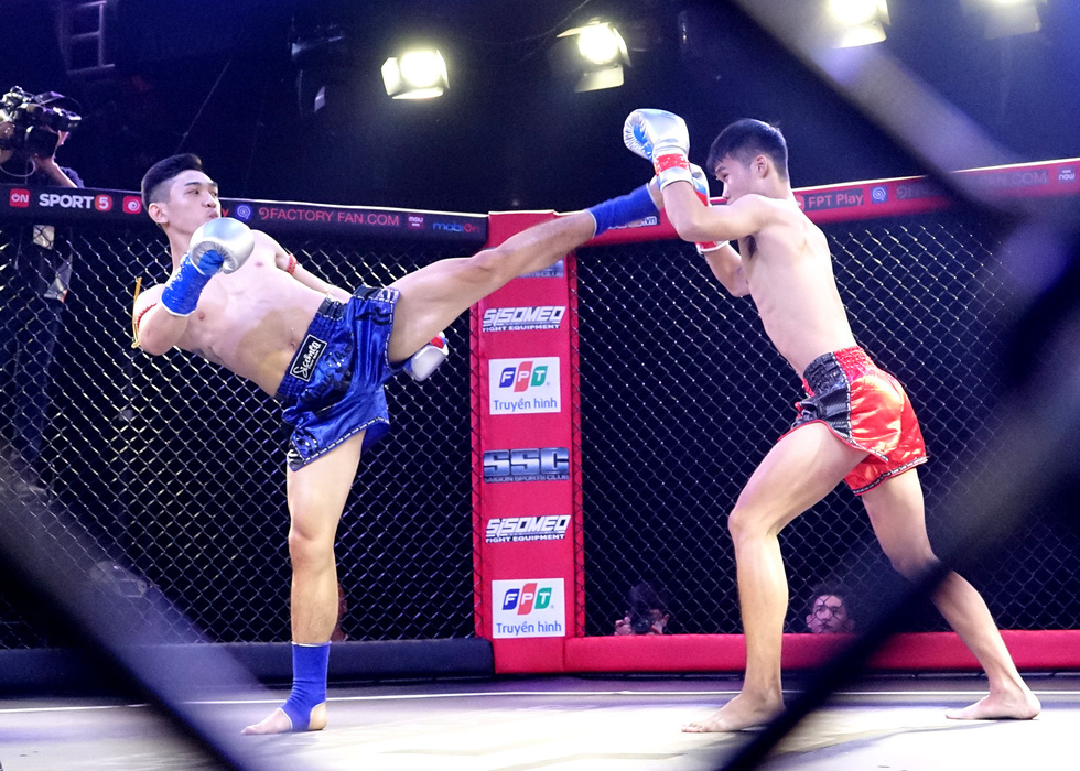 Huynh Hoang Phi (blue) and Do Huy Hoang (red) brawl in a kickboxing match in Bai Danh Chien 4 tournament. Photo: Hoang Tung / Tuoi Tre