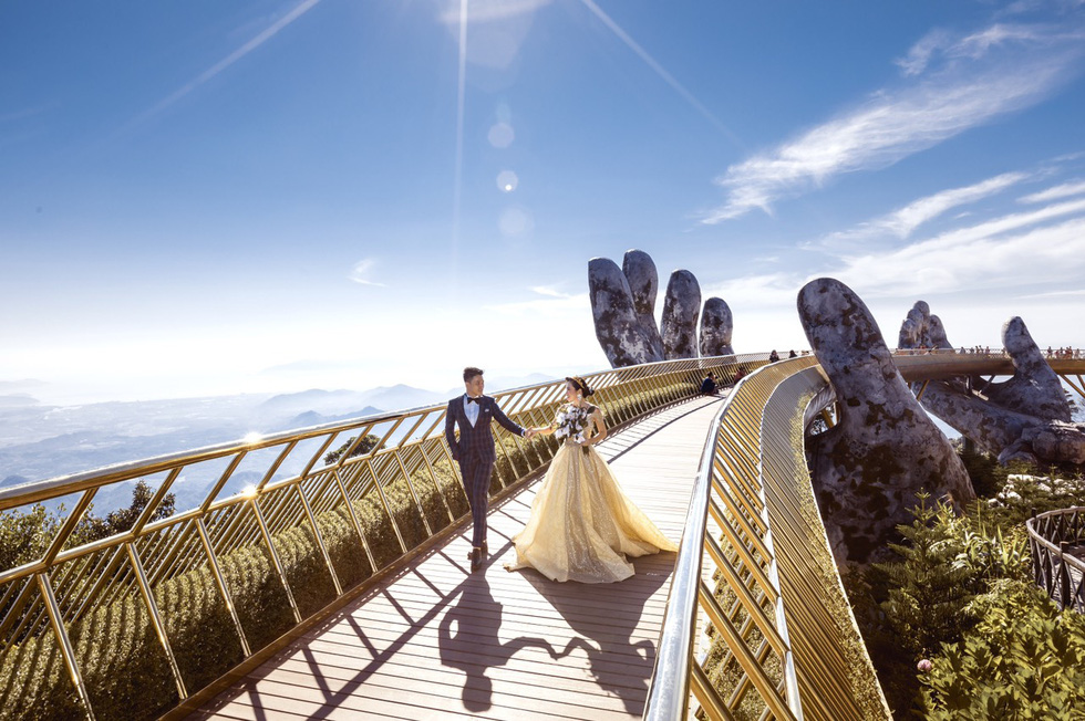 Newlyweds Hoang Anh and Quynh Hoa are seen in their pre-wedding photo taken on the Golden Bridge in Da Nang City.