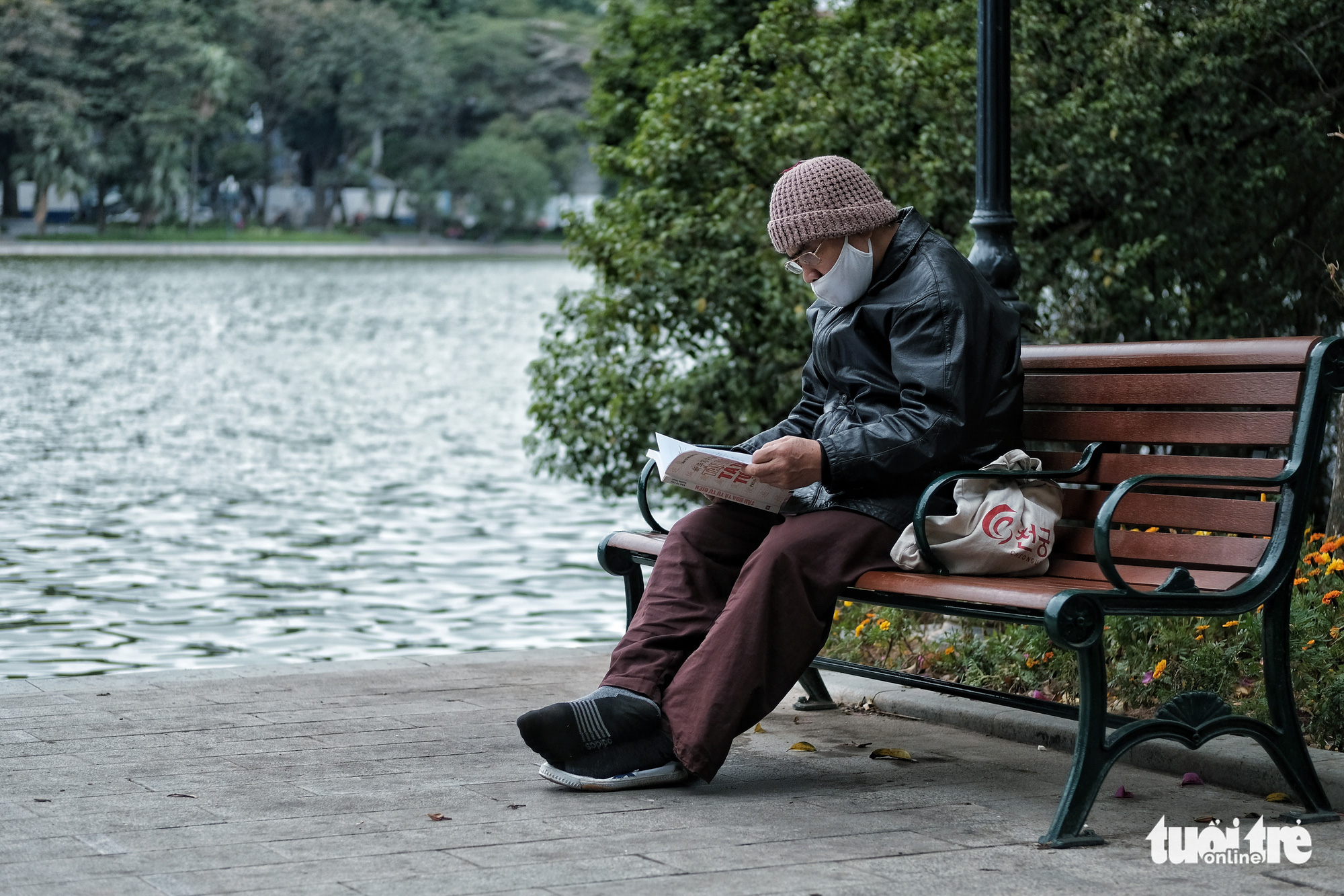 A man reads a book at Hoan Kiem Lake in Hanoi, December 15, 2020. Photo: Mai Thuong / Tuoi Tre