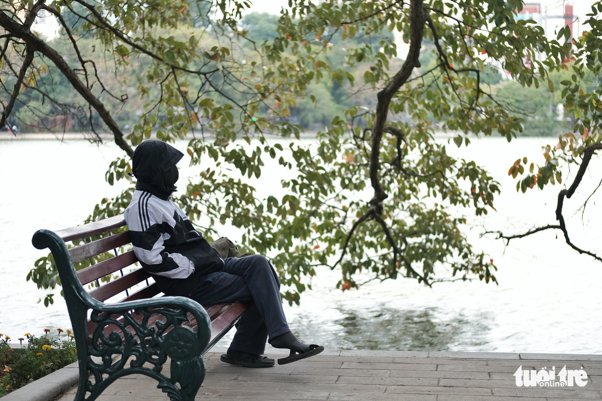 A resident sits on a bench at Hoan Kiem Lake in Hanoi, December 15, 2020. Photo: Mai Thuong / Tuoi Tre