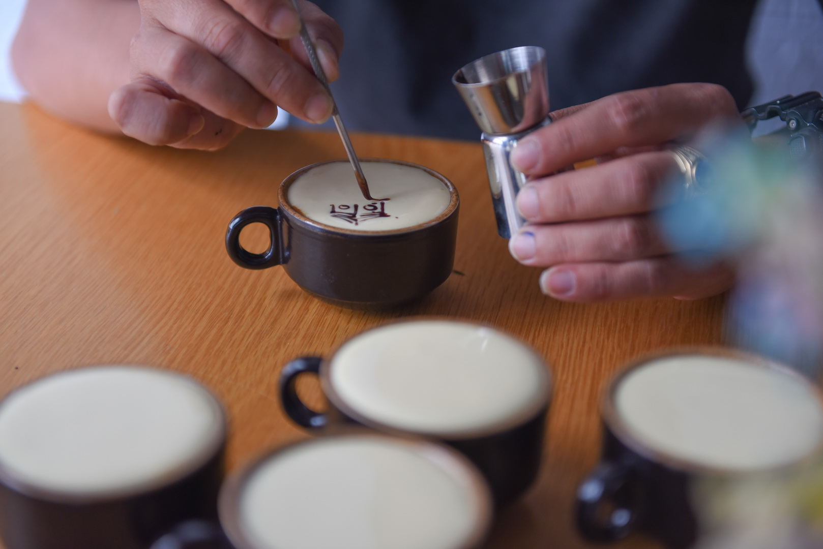Cao Truong Minh is sketching on a cup of egg coffee before serving it to a customer at his coffee shop in Ho Chi Minh City's Binh Thanh District. Photo: Ngoc Phuong/ Tuoi Tre