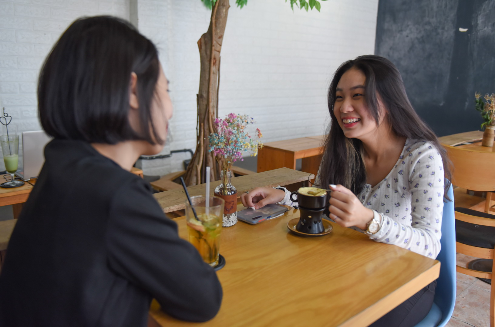 Nguyen Bao Ngan (right) from Thu Duc District enjoys egg coffee at Minh's shop. Photo: Ngoc Phuong/ Tuoi Tre