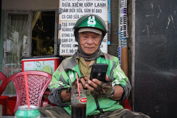Ngo Van Ut checks his phone between ride-hailing gigs. Photo: Kim Ut / Tuoi Tre