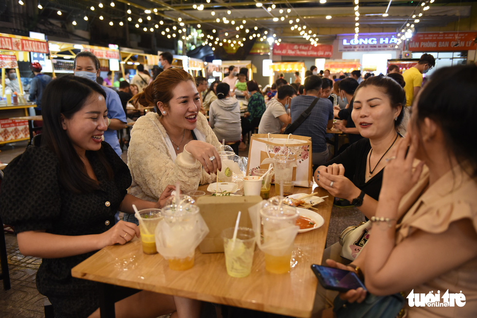 Women talk and laugh at the food section at the Ky Dai Quang Trung pedestrian street in District 10, Ho Chi Minh City. Photo: Ngoc Phuong / Tuoi Tre