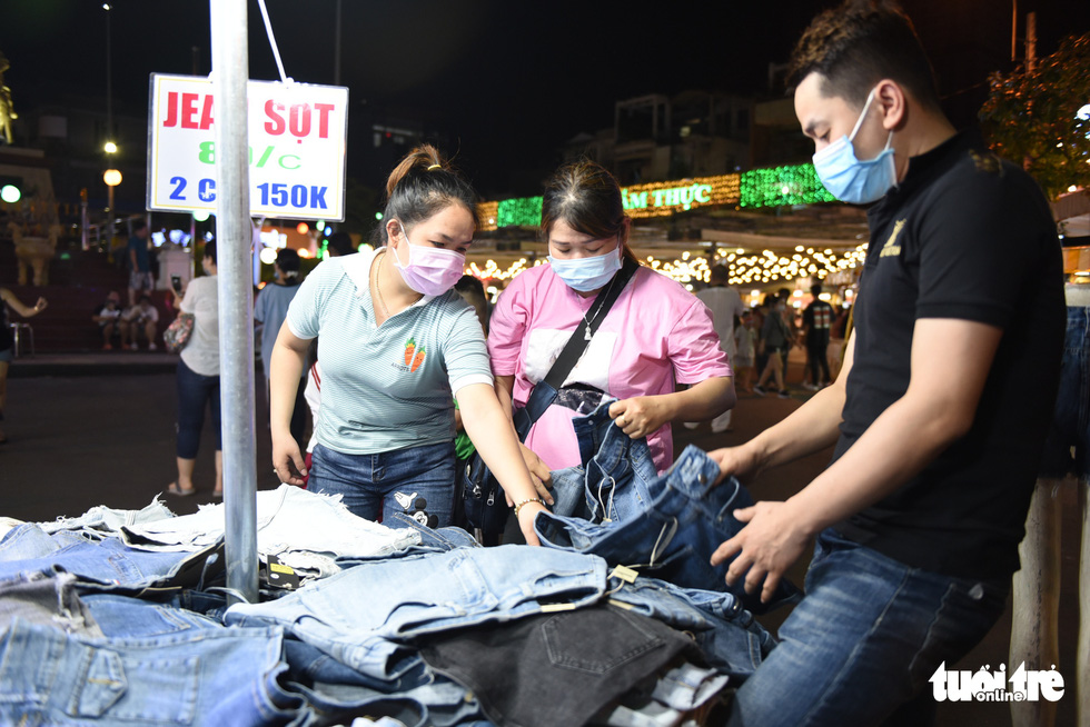 Two women choose jeans at one of 20 clothing kiosks at the night market at the Ky Dai Quang Trung pedestrian street in District 10, Ho Chi Minh City. Photo: Ngoc Phuong / Tuoi Tre