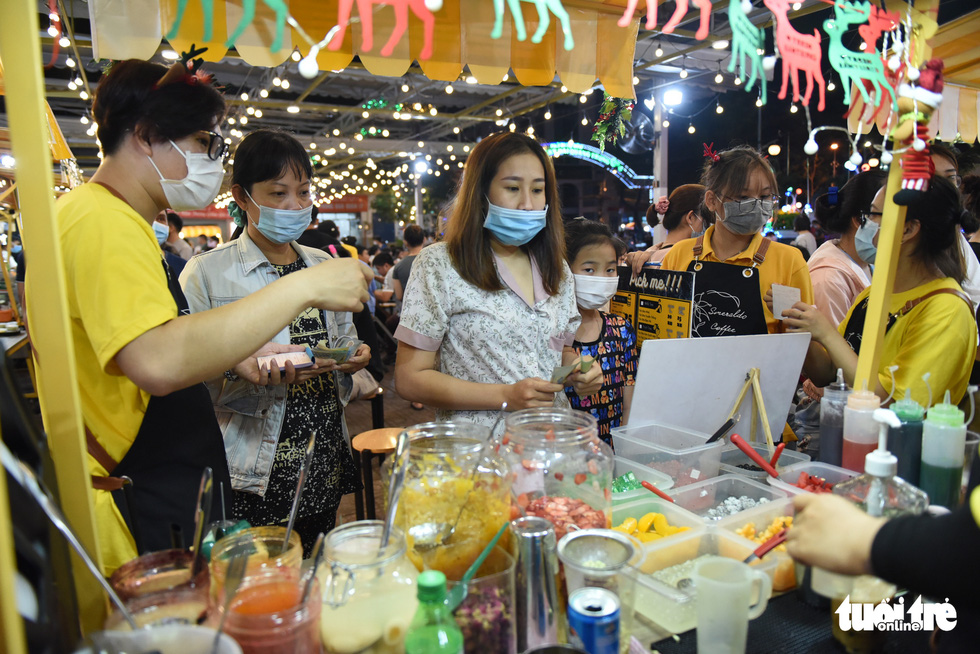 Some customers surround a street food kiosk at the Ky Dai Quang Trung pedestrian street in District 10, Ho Chi Minh City. Photo: Ngoc Phuong / Tuoi Tre