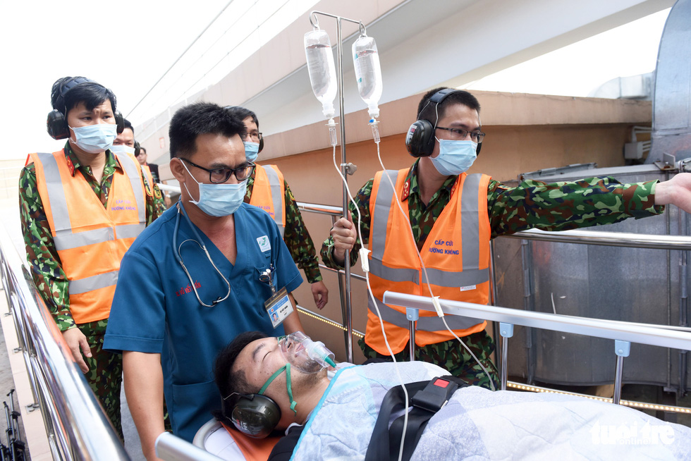Medical workers rush a patient to emergency room after receiving him from a helicopter that landed atop the Orthopedic Building at the Military Hospital 175 in Ho Chi Minh City during a hypothetical practice, December 19, 2020. Photo: Duyen Phan / Tuoi Tre