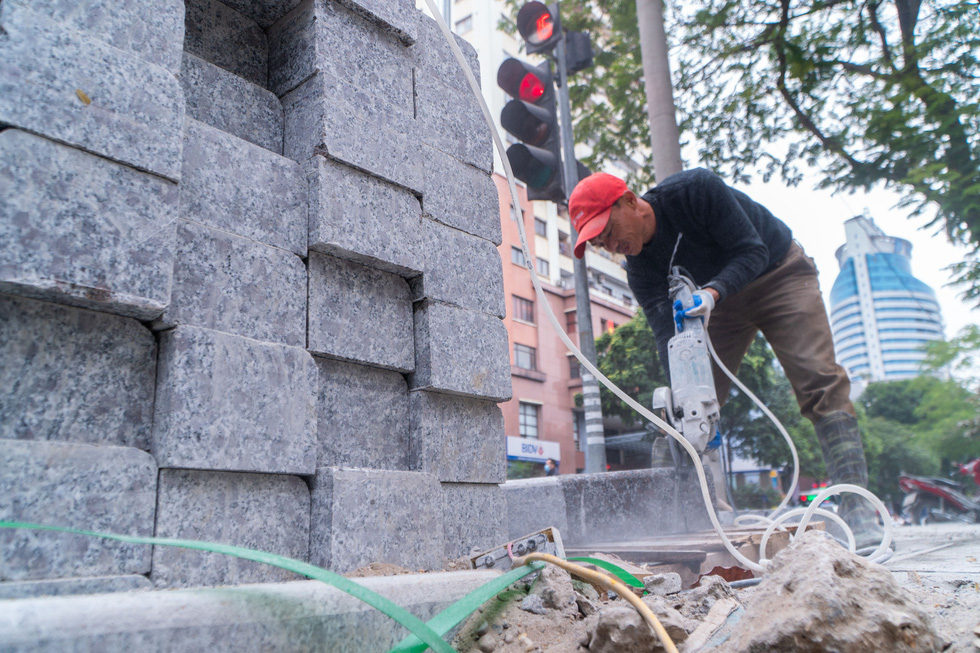 Construction workers install natural stone paving on Huynh Thuc Khang Street of Hanoi. Photo: Pham Tuan / Tuoi Tre