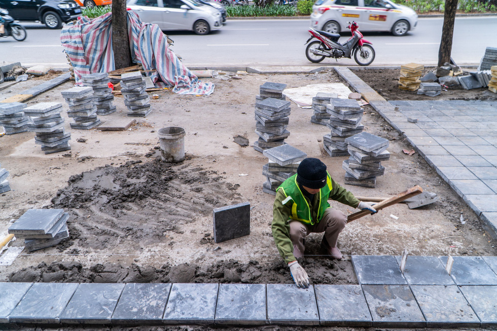 A construction worker installs natural stone paving on Nguyen Van Huyen Street of Hanoi. Photo: Pham Tuan / Tuoi Tre