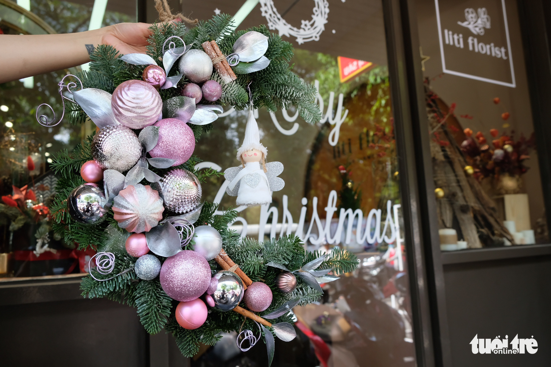 A Christmas laurel wreath made from fresh pine tree branches and ornaments is decorated at a store in Ho Chi Minh City. Photo: Bong Mai / Tuoi Tre