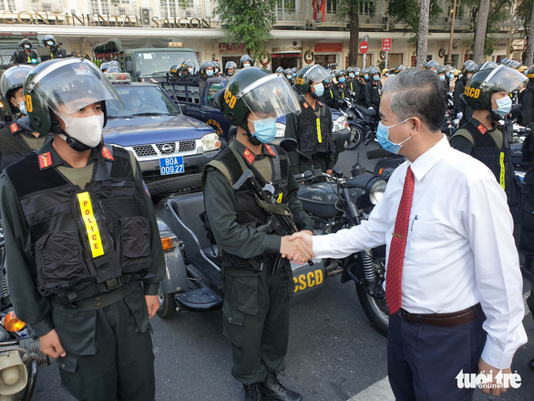 Ngo Minh Chau (right), deputy chairman of the Ho Chi Minh City People's Committee, shakes hands with a member from the city's mobile police unit, December 15, 2020. Photo: Minh Hoa / Tuoi Tre