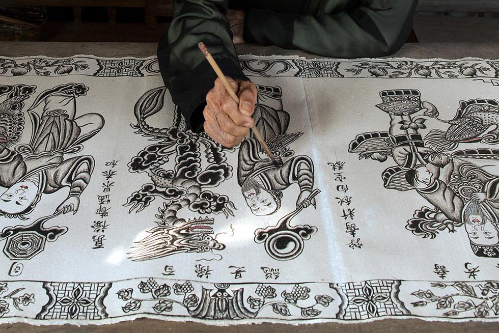 Nguyen Dang Che inks on a Dong Ho print. Photo: Hoang Ngoc Thach