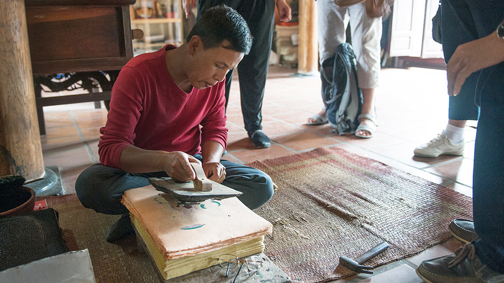 A craftsman prints Dong Ho painting by pressing the mold on Do paper. Photo: Hoang Ngoc Thach