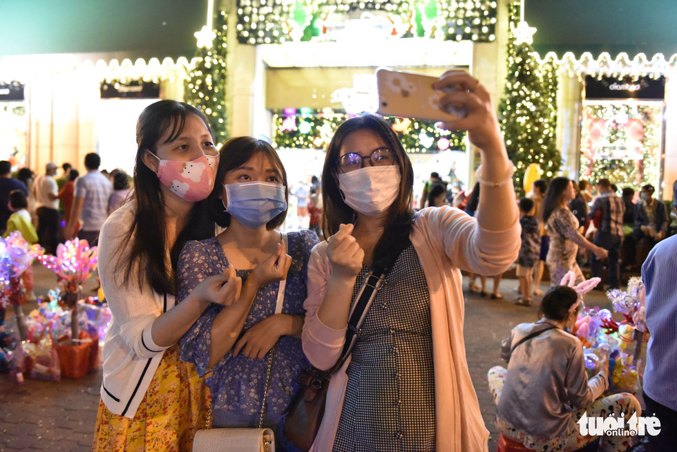 A group of friends take a selfie amidst the Christmas decoration background in District 1, Ho Chi Minh City. Photo: Ngoc Phuong / Tuoi Tre