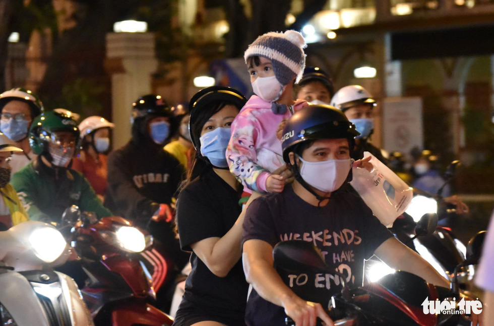 A child wears a mask and warm clothes while going out with parents. Photo: Ngoc Phuong / Tuoi Tre