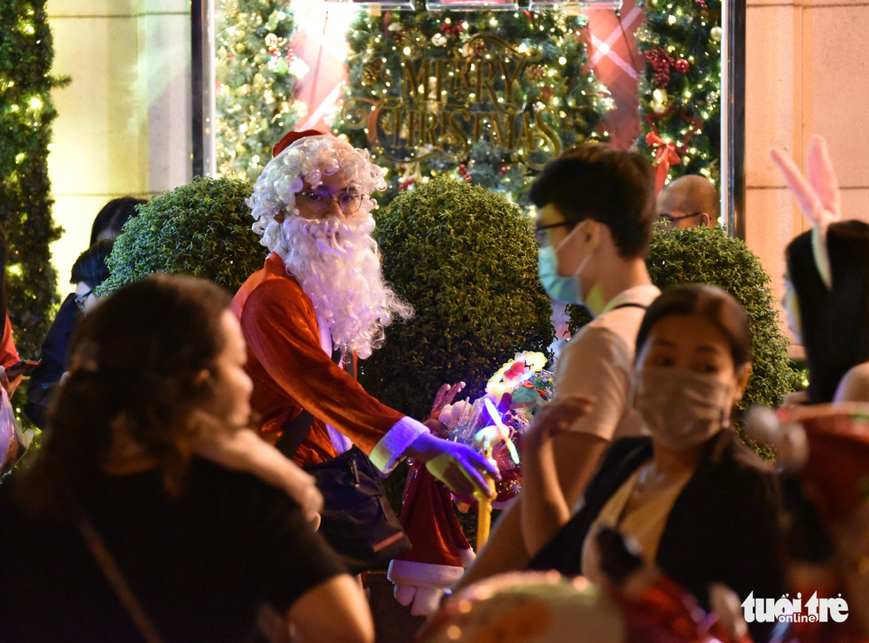 A man dressed up as Santa Claus to sell souvenirs is seen in the photo. Photo: Ngoc Phuong / Tuoi Tre