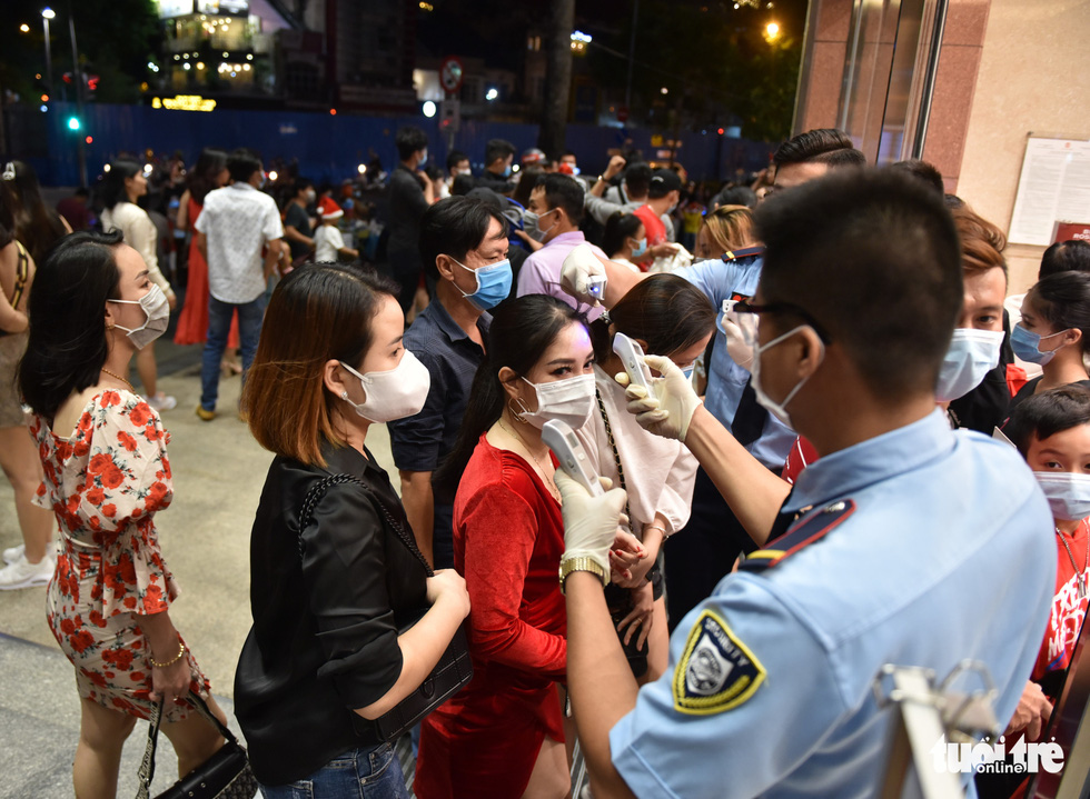 A security guard conducts temperature checks and reminds customers to wear masks when entering Takashimaya department store, District 1, Ho Chi Minh City. Photo: Ngoc Phuong / Tuoi Tre