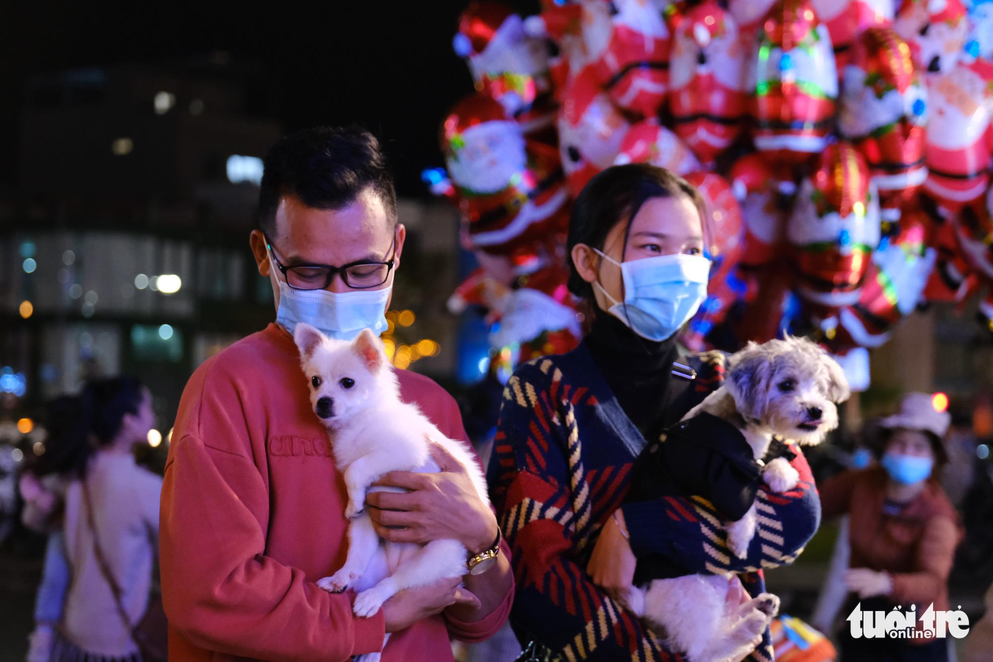 A couple brings their pets to downtown Da Nang City to mark Christmas Eve, December 24, 2020. Photo: Tan Luc / Tuoi Tre