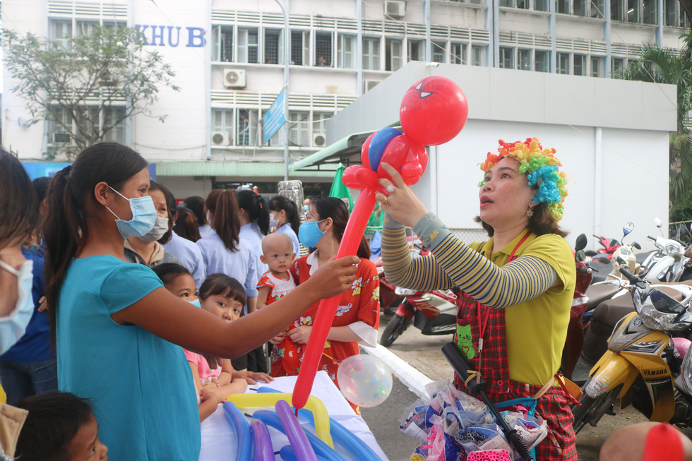 A woman dressed a clown costume gives away twisted balloons to young inpatients at Ho Chi Minh City Oncology Hospital, December 24, 2020. Photo: Thu Hien / Tuoi Tre