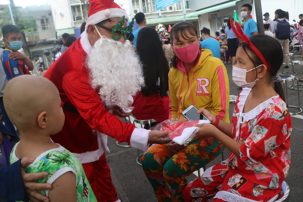 A man dressed in a Santa Claus costume gives a Santa hat to a child inpatient at Ho Chi Minh City Oncology Hospital, December 24, 2020. Photo: Thu Hien / Tuoi Tre