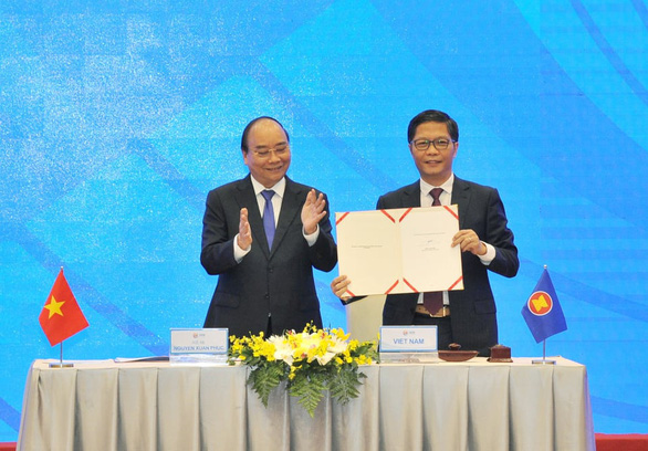 Vietnam's Prime Minister Nguyen Xuan Phuc (left) and Minister of Industry and Trade Tran Tuan Anh (right) react at the signing ceremony of the Regional Comprehensive Economic Partnership (RCEP) Agreement on November 15, 2020. Photo: D.Dung / Tuoi Tre